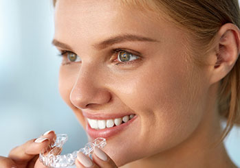 Female holding clear aligners